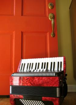 Photo of a red accordion next to a red door